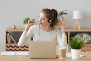 Joyful young millennial woman wearing headset with microphone sitting at the desk at home or office opposite computer enjoy music and singing. Student studying online e-learning or worker has a break