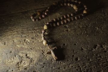 A wooden rosary on an old wooden background