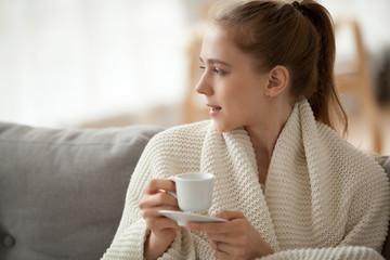 Profile of attractive millennial woman sitting on couch at home looking at window enjoying the morning. Young female wearing warm white knitted sweater holding cup drinking black coffee hot beverage