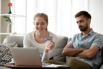 Unsatisfied husband looking at smiling wife, girl holding credit card choose goods on internet online making shopping wasting money using laptop sitting at home. Extra expenses and big spender concept