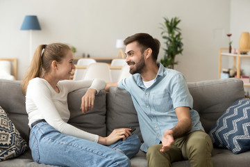 Affectionate cheerful married couple in love or friends spend free time together on weekend talking laughing communicating sitting in living room at home. Dating and not boring with each other concept