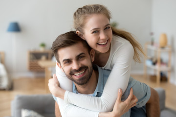 Head shot happy millennial young man and woman hugging embracing indoors. Portrait close up smiling husband and wife piggyback ride looking at camera laughing. Dating and romantic relationship concept