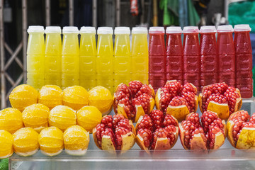 Fresh cold drink, Fresh Pomegranate, orange and lemon fruit for making juice on the counter of the street market in Chinatown, Bangkok, Thailand. Thai tropical juice for sale.
