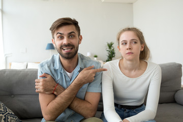 Millennial married couple sitting together on couch in living room at home. Boyfriend and girlfriend having video call funny male pointing on dissatisfied female complains talking with friends