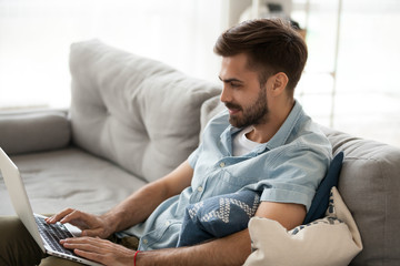Young millennial positive man sitting on couch in living room with laptop alone on weekend at home. Handsome male using notebook have fun looking recreational video or freelancer working online indoor