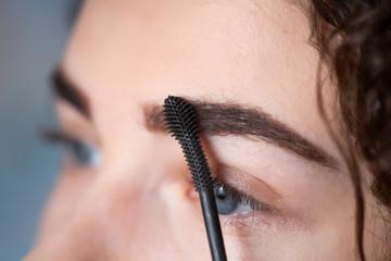 Young woman undergoing eyebrow correction procedure. Eyebrow Mascara