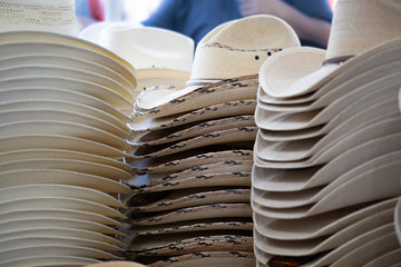 An isolated point of view of a retail display of stacks of summer cowboy hats