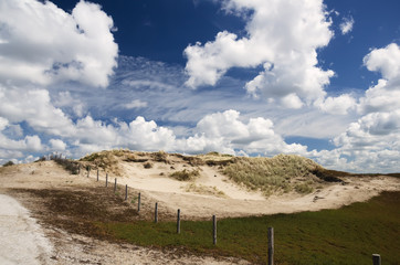 Landscape in the dunes with dunes grass, sand and meadows against a blue sky with beautiful clouds.