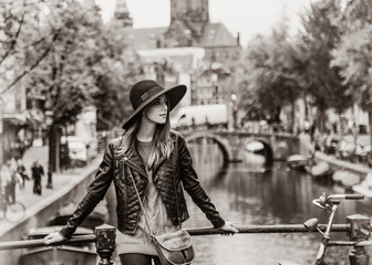 Redhead in hat staying on bridge in Amsterdam. Image in black and white color style