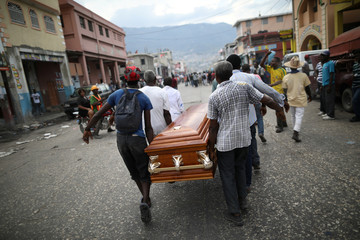 Men carry a coffin during a funeral, turned into a protest, for four people who, according to the mourners, died during clashes on October 17, in the streets of Port-au-Prince