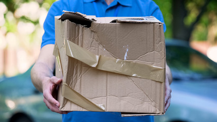 Obraz Male courier showing damaged box, cheap parcel delivery, poor shipment quality - fototapety do salonu
