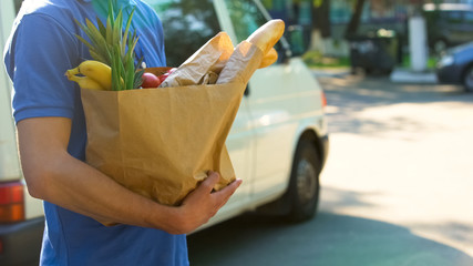 Delivery worker holding grocery bag with fresh tasty goods, supermarket service