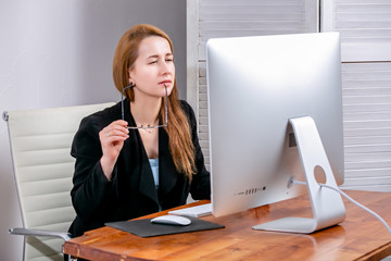 Portrait of happy young successful businesswoman at office. She is sitting at the table, holding her glasses and looking thoughtfully at display. Black Friday or Cyber Monday. Selecting items