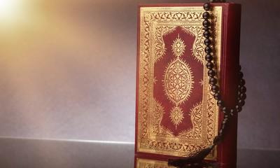 Islamic Book Koran with rosary on grey