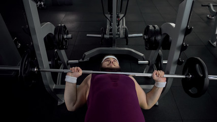Chubby man unable to lift heavy barbell in gym during sport exercise, health