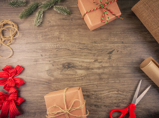 Christmas gift box and wrapping tools flat lay on wooden background with copy space