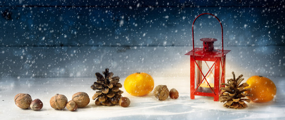 wide christmas decoration background with a red candle light lantern, tangerines, cones and nuts in the snow on rustic wood at night, panoramic format with copy space,