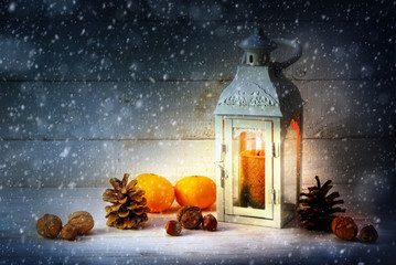 christmas decoration with a candle light lantern, tangerines, cones and nuts in the snow on rustic wood at night,  copy space