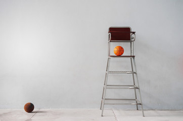 chair of sport referee with orange basketball in gymnasium gray cement background