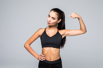 Cheerfully smiling fitness sporty woman demonstrating biceps isolated on white background