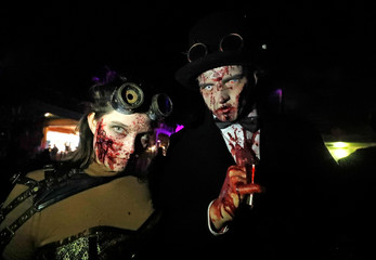 Participants in costume and make-up pose for a photo during a Halloween parade at Walibi park in Wavre