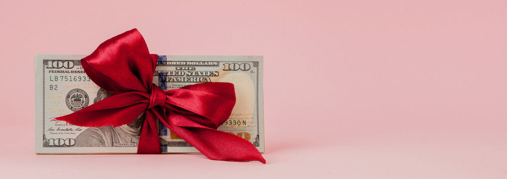 one hundred dollars gift wraped with a red ribbon on pink background