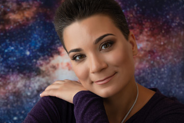 A young woman astrologer with smooth skin and short, striped hair smiles and puts her hand on her shoulder. Photo on the cosmic space background.
