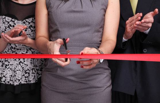 Businesswoman cutting red ribbon while other people next to her are clapping hands