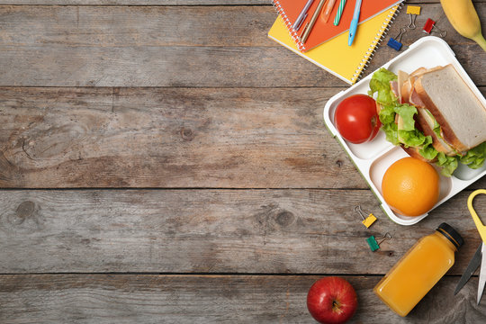 Flat lay composition with healthy food for school child and space for text on wooden background