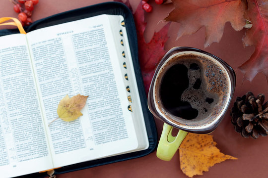 Hot coffee and book Bible on natural autumn background.