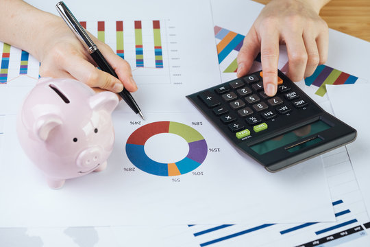 Hand holding pen reviewing pie chart and graph report with calculator and pink piggy bank on table, finance, money budget planning or investment asset allocation concept
