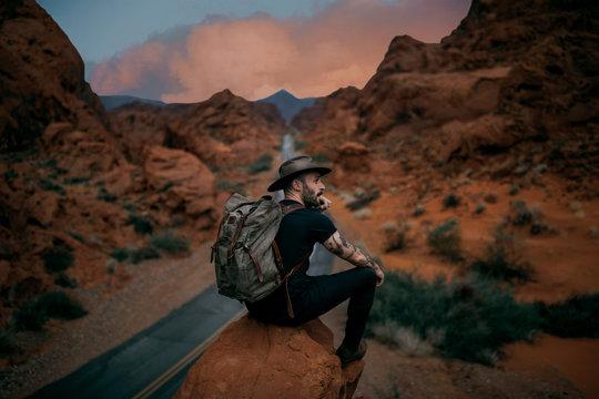 Man wearing hat sitting on rock during sunset