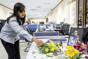 A woman employee of PT Timah Tbk., puts a flower at the desk of her colleague, passenger of Lion Air flight JT610, in Pangkal Pinang