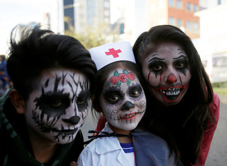 People in costume pose for a photograph during Halloween celebrations in La Paz