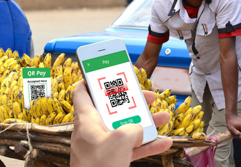 Hand holding smartphone to scan QR code payment , online shopping , Smart cashless technology concept.