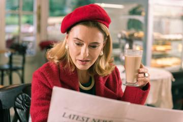 Morning newspaper. Mature French elegant stylish woman reading morning newspaper sitting in bakery