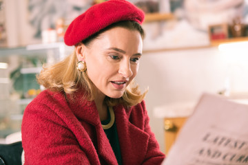 Woman with newspaper. Elegant mature French woman wearing beret reading newspaper sitting in bakery