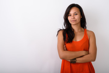 Studio shot of young Asian woman with arms crossed against white