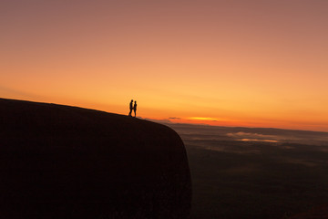 Silhouette couple  so sweet standing on the hill at sunrise morning time  at Bueng Kan Thailand.