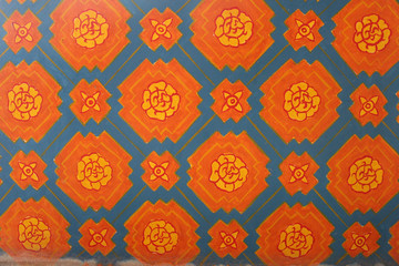 Weathered orange and blue floral pattern painted on the wall of an ancient temple in Thailand