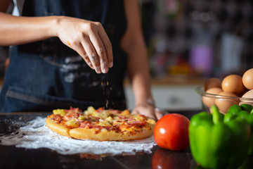 Closeup of  hand female wears apron,sprinkle with flour as prepares delicious pizza, going to make surprise for family and treat with tasty pastry, Baking concept.
