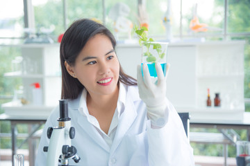 Beautiful asian laboratory worker holding beaker with plant in laboratory.