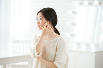 Beautiful Korean girl touching soft skin of her face with finger