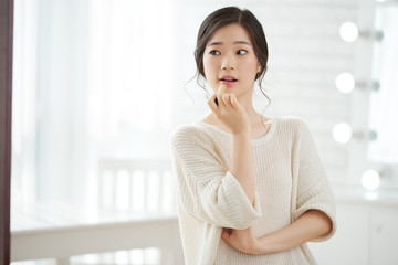 Beautiful young Asian woman applying pink lip balm