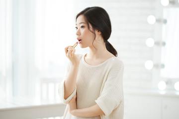Pretty young Kirean woman applying pink lipstick