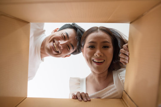 Happy couple opening a box and looking inside to product