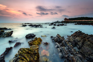 A Long exposure picture of golden sunrise with stone jetty