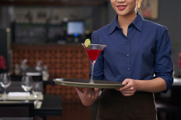 Cropped image of waitress holding tray with cocktail on it