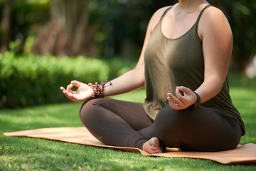 Woman sitting in lotus position on yoga mat in summer park