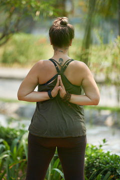 Rear view of young woman doing hands behind back yoga clasp